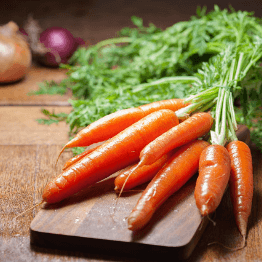 bunch of carrots with an onion in the background
