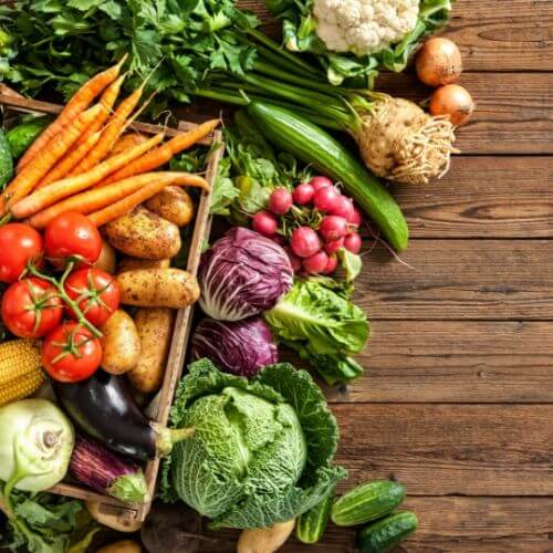 a large selection of fresh vegetables on a wood background